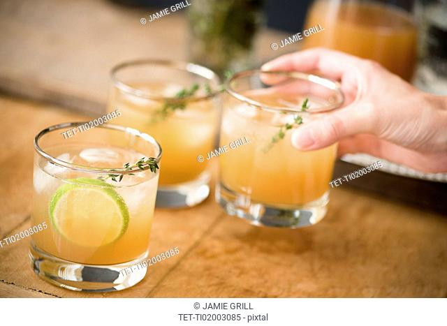 Woman's hand holding drinking glass with cocktail