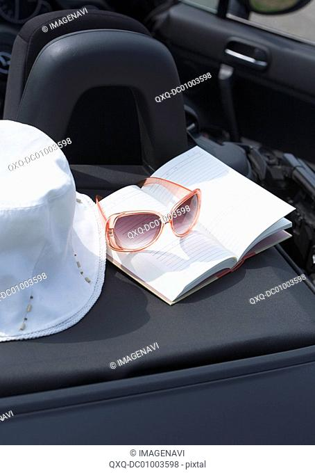 Hat and sunglasses on the book
