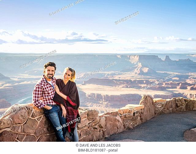 Hispanic couple smiling on remote hilltop