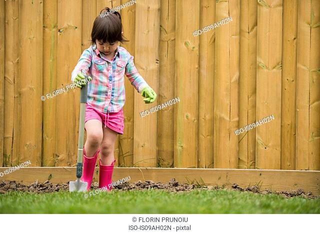 Young girl digging soil in the garden