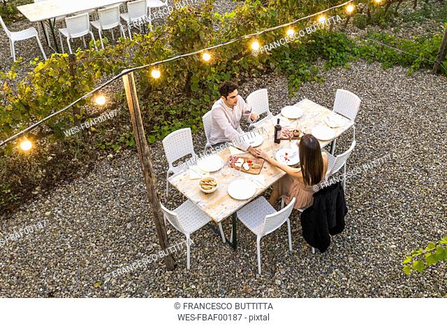 Italy, Tuscany, Siena, young couple having a romantic dinner in a vineyard