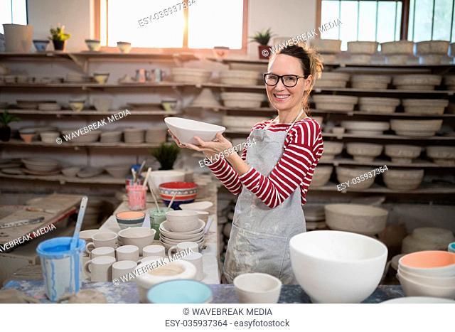 Portrait of female potter holding bowl
