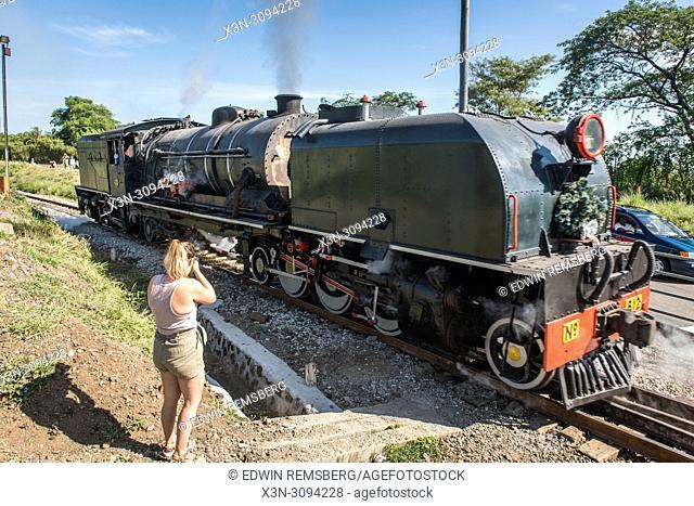 A woman takes a snapshot of a Garratt steam locomotive crossing the Victoria Falls Bridge. Zimbabwe
