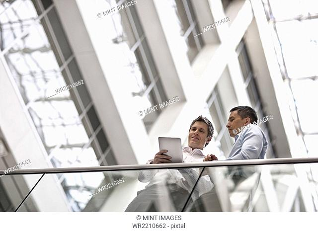 Two men, business colleagues, standing by a railing in an atrium or courtyard, looking at a digital tablet