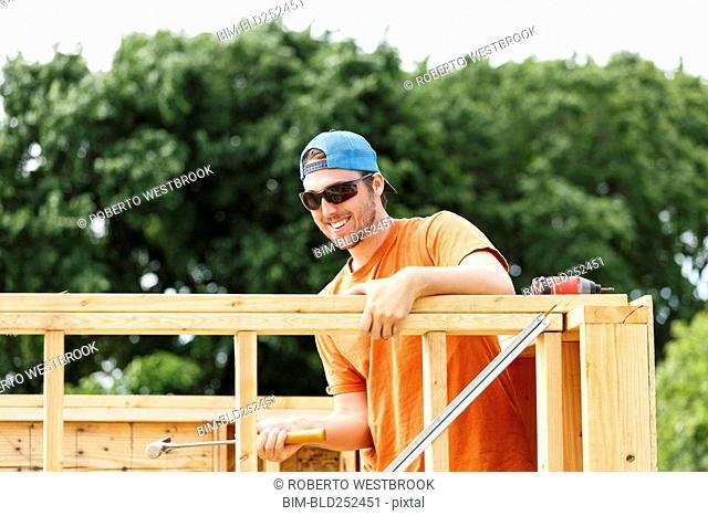 Caucasian man hammering at construction site