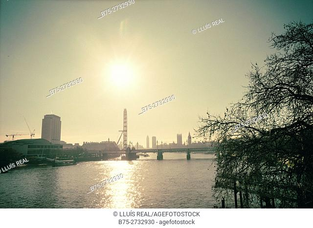 Backlit view of the City of London with Shell Centre building, London Eye, Big Ben, Westminster Bridge, London, England