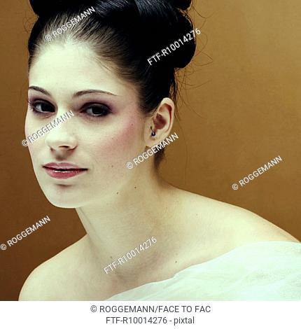 Young brunette woman with a pinned up hairstyle