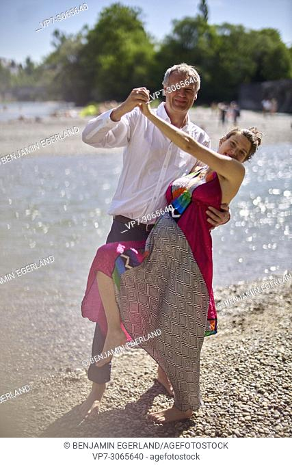 Couple dancing, pregnancy, age difference. At river Isar, Munich, Germany