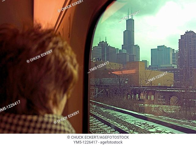 Woman looking out Metra train window at the Sears Tower Willis Tower on her way into Chicago