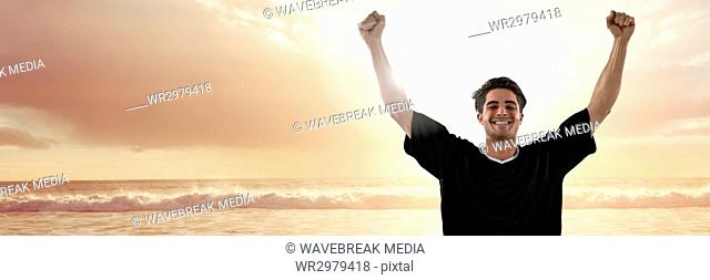 Man in jersey celebrating on sunset beach with flare