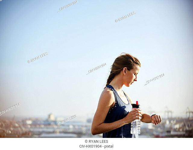 Female runner with water bottle checking smart watch fitness tracker under sunny bleu sky