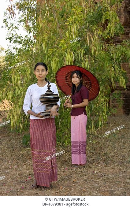 Young Burmese woman holding a lacquered jar, a second Burmese woman with a red parasol at back, Bagan, Myanmar