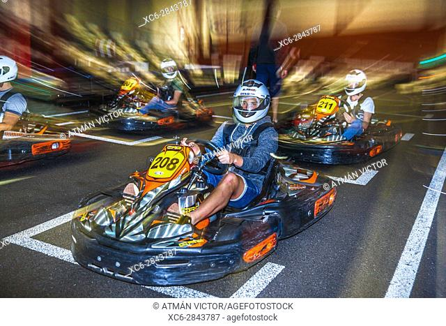 young men driving karts inside the Karting Indoor circuit in Santa Cruz de Tenerife city