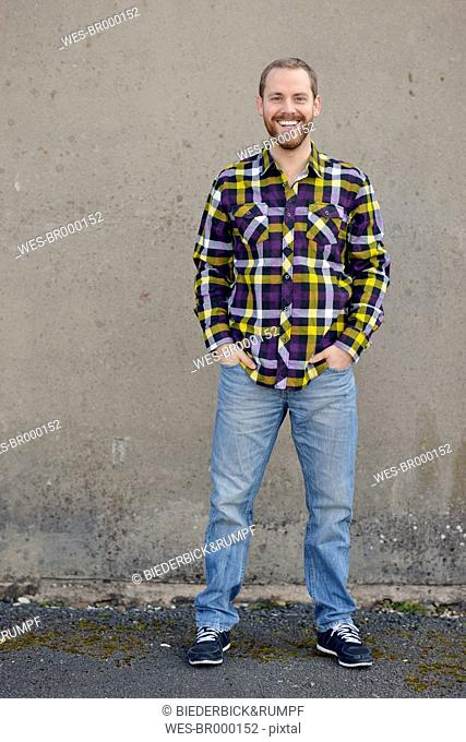 Laughing young man wearing checkered shirt and jeans
