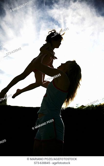 Mother and daughter in backlight