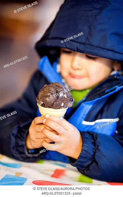A 4 year old Japanese American boy holds an ice cream cone filled with chocolate ice cream