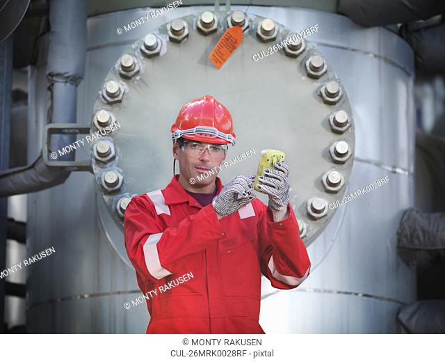 Worker with gas sensor at storage plant