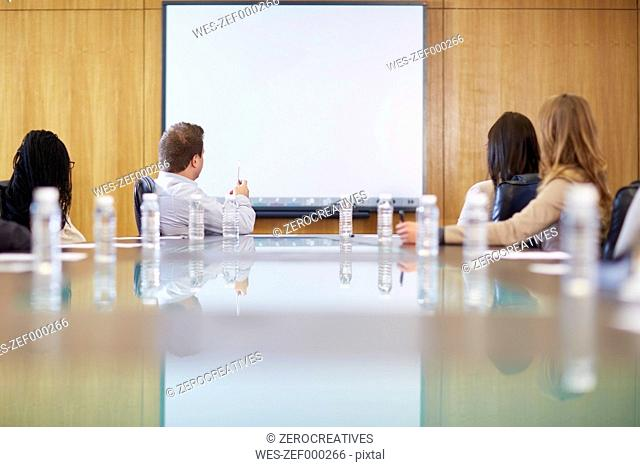 Group of businesspeople looking at empty whiteboard in boardroom