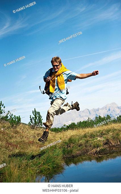 Austria, Salzburger Land, Man jumping by waterside, laughing, portrait