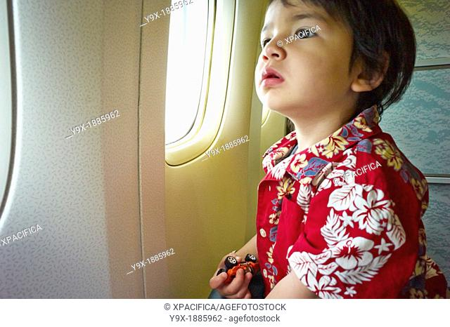 A young boy in a Hawaiian shirt looking out of a plane window