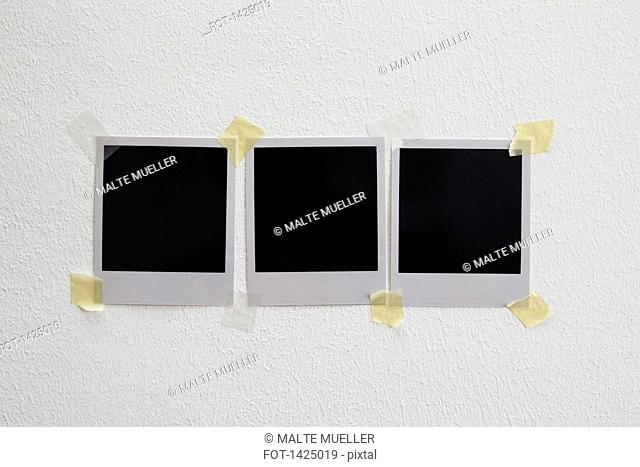 Blank photo prints stuck on wall