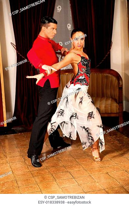 Young dance couple preforming latin show dance in ancient ballro