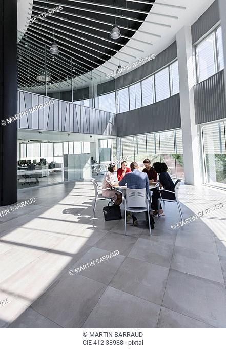 Business people meeting at table in modern office atrium