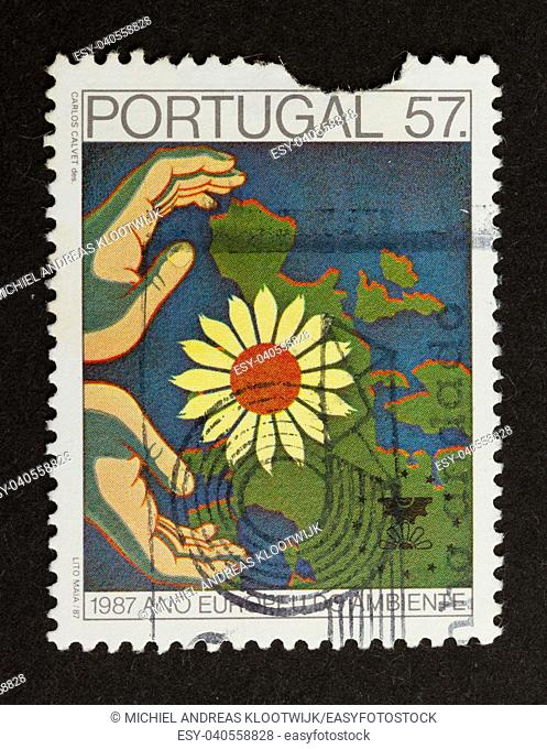 PORTUGAL - 1987: Stamp printed in Portugal shows a map of europe with a flower an hands, 1987