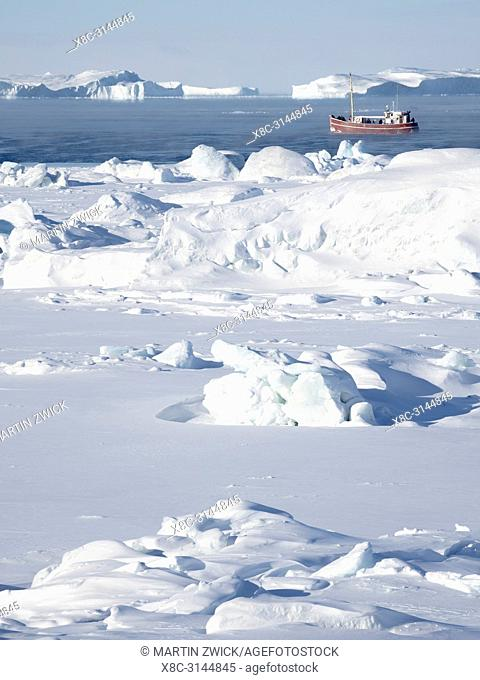 Boat on the frozen Disko Bay with icebergs at the Ilulissat Icefjord . The icefjord is listed as UNESCO world heritage. America, North America, Greenland