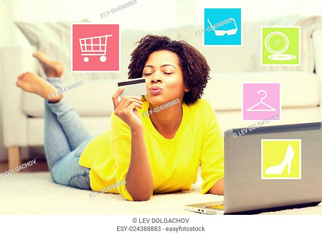 people, internet bank, online shopping, technology and e-money concept - happy african american young woman lying on floor with laptop computer and credit card...