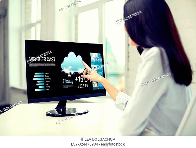business, people, technology and meteorology concept - close up of woman with weather cast and world news on computer monitor in office