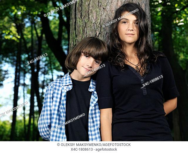 Emotional portrait of a teenage sister and a younger brother standing together leaning against a tree in the nature