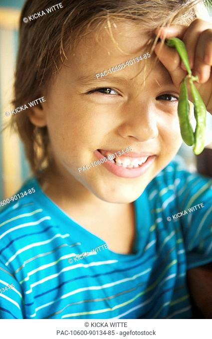 Hawaii, Kauai, Kilauea, Young boy sitting on porch eating soybeans