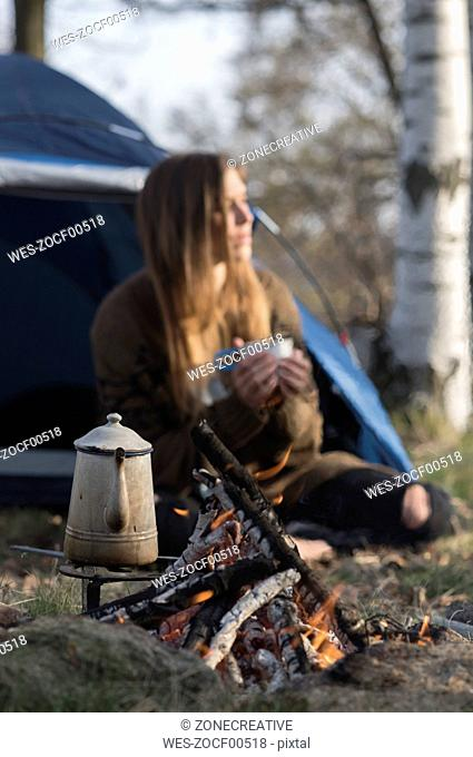 Woman camping at campfire in forest