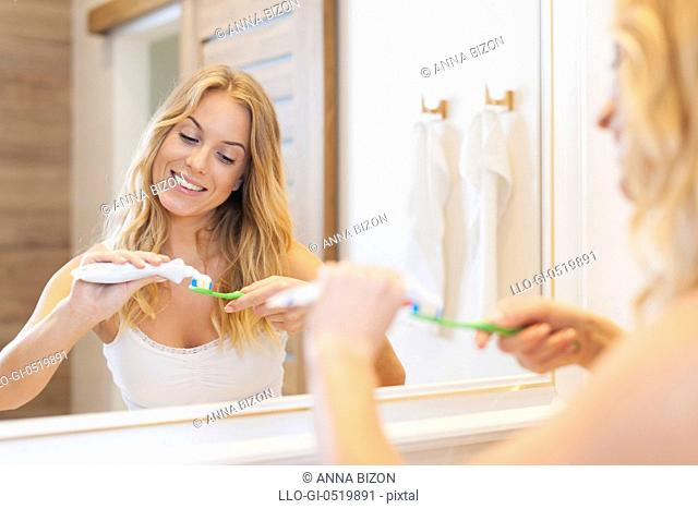 Beautiful woman brushing teeth in bathroom. Debica, Poland