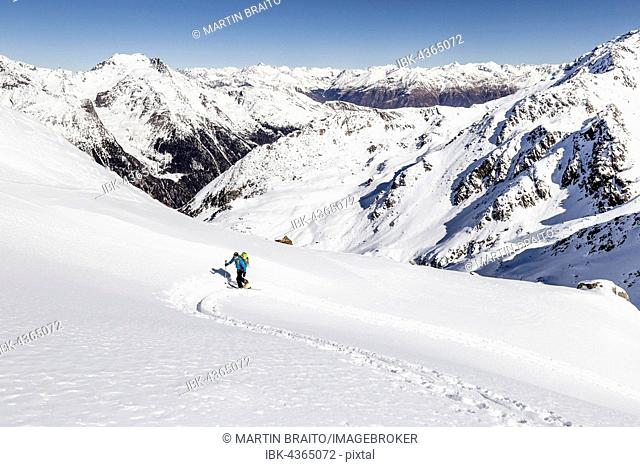 Ski tourer ascending Hintere Nonnenspitze, below Martello, in the background the Vinschgau and the Main Chain of the Alps, Martell, Vinschgau