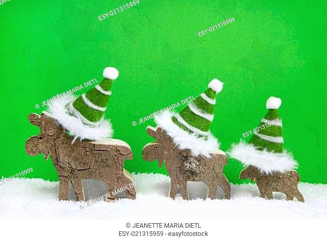 Reindeer family on green and white wooden christmas background with santa hats