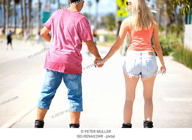 Couple rollerblading outdoors, holding hands, rear view