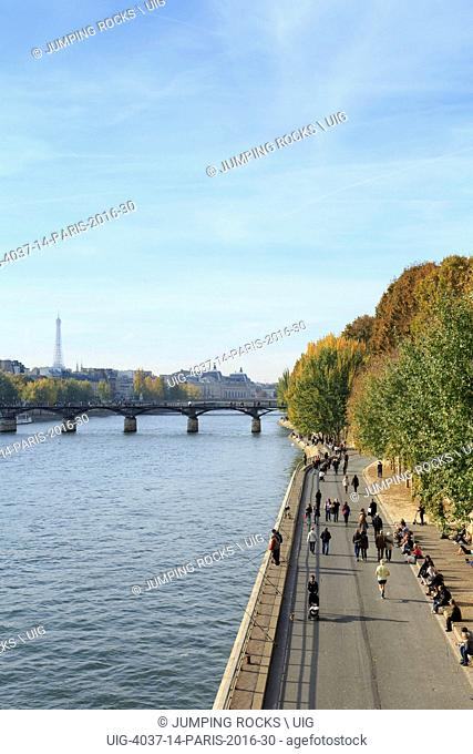 Pedestrians walking along Seine in Autumn, Paris, France