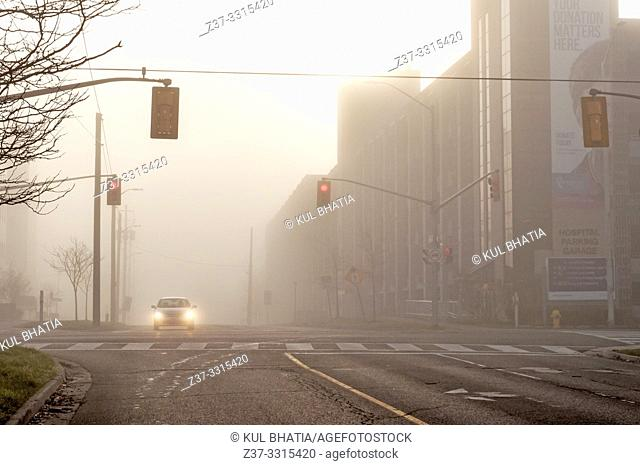 One car stopped at a red traffic light at an intersection in heavy fog, Canada