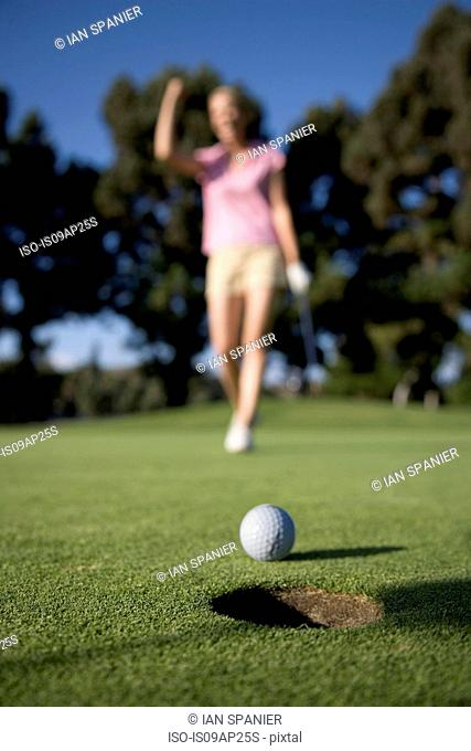 Golf ball on edge of hole in front of woman golfer celebrating