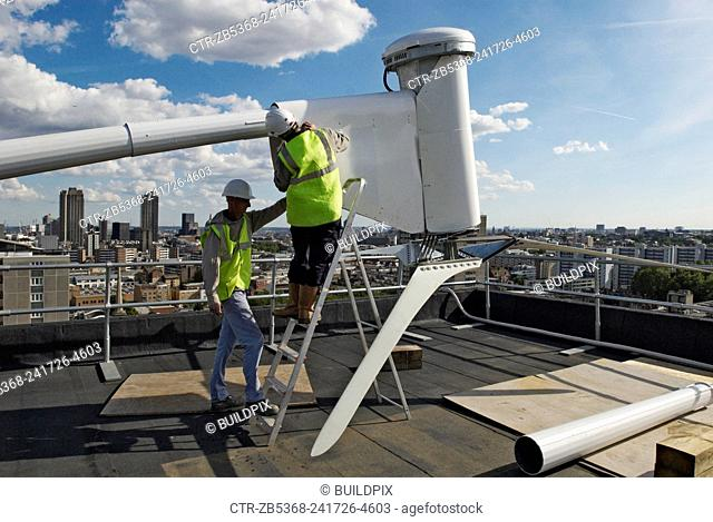 Erecting a wind turbine on a roof of a housing block of flats, City Road, London, UK