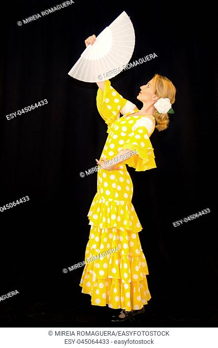 Flamenco dancer dressed in yellow with white fan