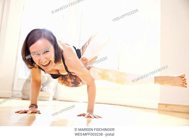 Woman in sunny yoga studio holding Galavasana pose