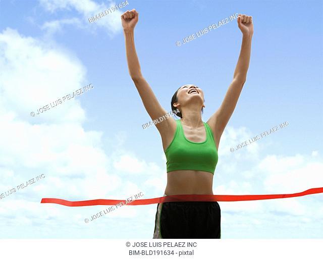Chinese runner crossing finish line