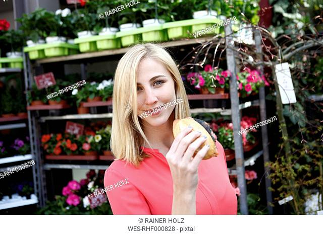 Smiling blond woman with wheat roll on weekly market