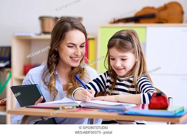 Smiling teacher with schoolgirl in class