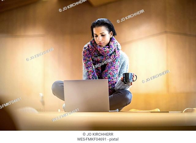 Portrait of fashionable young woman with cup of coffee sitting on conference table using laptop