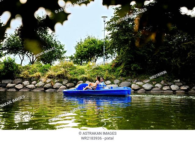 Friends pedal boating on river