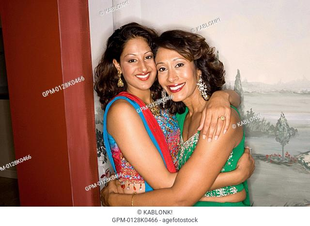Portrait of mother and daughter in traditional sari dress hugging each other, looking at camera